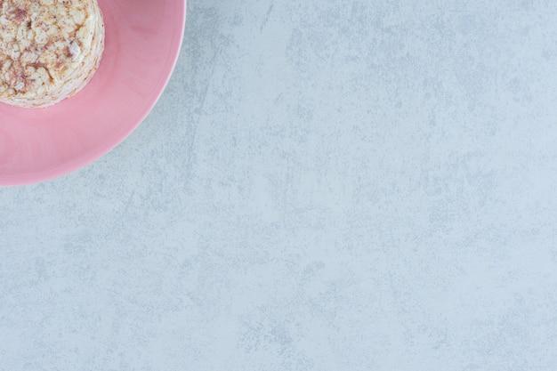 Dmuchane ciastka ryżowe i słodki krakers w talerzu na marmurze.