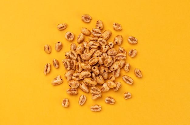 Dmuchane płatki pszenne na żółtym, miodowym ryżu powietrznym