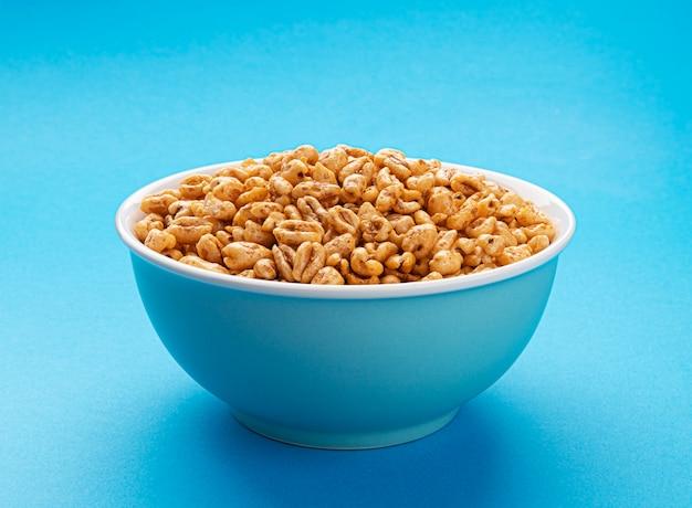 Dmuchane płatki pszenne w misce na niebieskim, miodowym powietrzu ryżowym