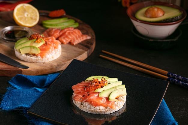 Dmuchany ryż posmarowany surowym łososiem i awokado na ciemnym stole