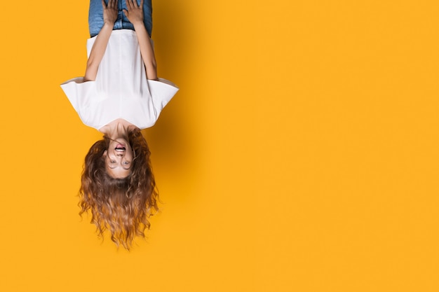 Do góry nogami zdjęcie kaukaskiej kobiety w białej koszuli i dżinsach uśmiechniętej na żółtej ścianie z wolną przestrzenią