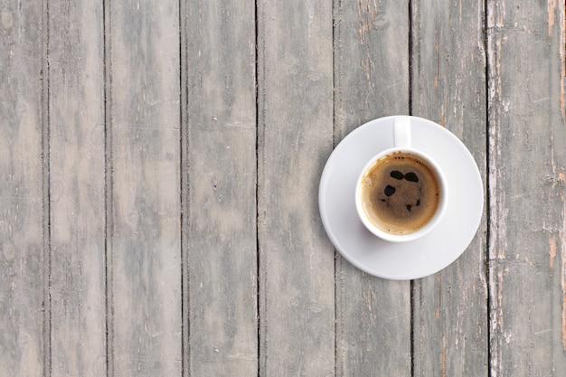 Do góry widok czarnego espresso na ciemnym drewnianym stole vintage. dodano miejsce kopiowania tekstu, odpowiednie dla tła koncepcji jedzenia lub picia.