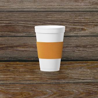 Do góry widok filiżanki kawy z papierowym uchwytem na białym tle na drewniane tła.
