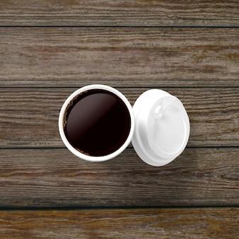 Do góry widok filiżanki kawy z pokrywką na białym tle na drewnianym tle.