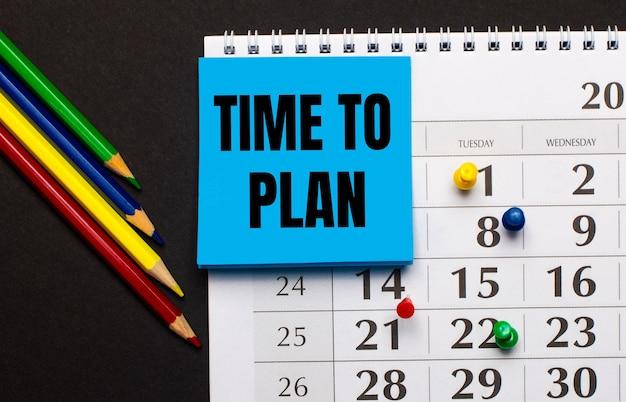 Do kalendarza dołączono jasnoniebieską kartkę z napisem time to plan. w pobliżu kolorowe kredki na ciemnym tle. widok z góry