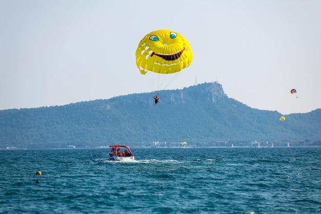 Do łodzi przyczepiony jest żółty spadochron z turystą, który latem lata po błękitnym niebie