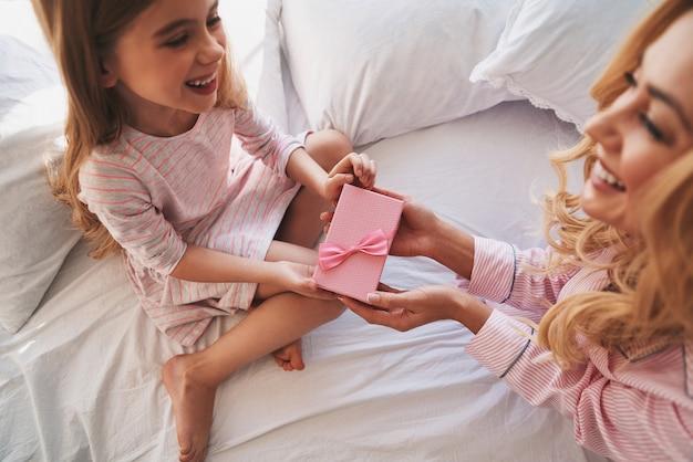 Do moich książąt. widok z góry młodej atrakcyjnej matki dającej prezent swojej uroczej córeczce siedząc na łóżku w domu
