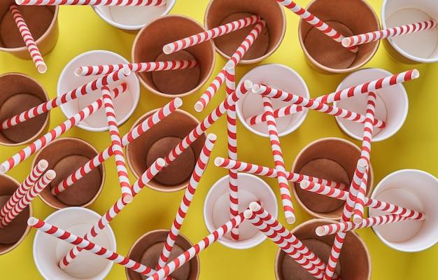 Do picia czerwone rurki słomki wykonane z papieru i skrobi kukurydzianej w pustych papierowych kubkach do kawy na modnym żółtym tle. koncepcja braku odpadów i plastiku. widok z góry.