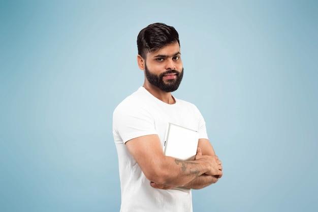 Do połowy długości bliska portret młodego człowieka hinduskiego w białej koszuli na niebieskiej przestrzeni