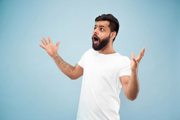 Do połowy długości bliska portret młodego człowieka hinduskiego w białej koszuli na niebieskiej ścianie. ludzkie emocje, wyraz twarzy, koncepcja reklamy. negatywna przestrzeń. zszokowane, zdziwione lub szalone szczęśliwe uczucia.