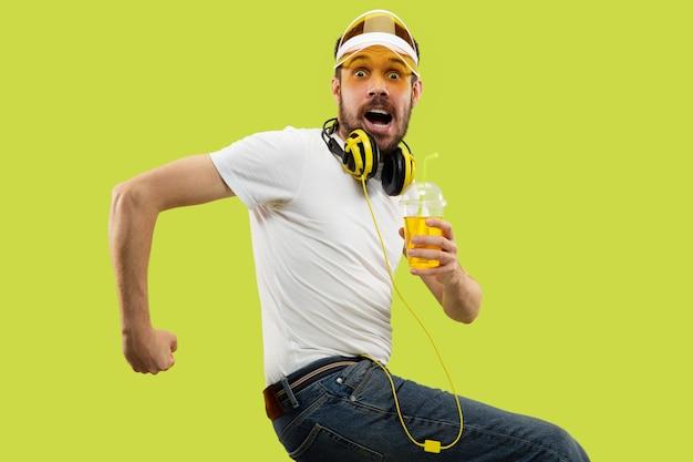 Do połowy długości bliska portret młodego człowieka w koszuli na żółtej przestrzeni
