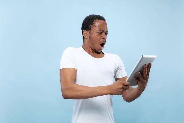 Do połowy długości bliska portret młodego mężczyzny afro-amerykańskiego w białej koszuli na niebieskiej przestrzeni