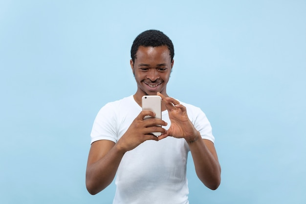 Do połowy długości bliska portret młodego mężczyzny afro-amerykańskiego w białej koszuli na niebieskim tle. ludzkie emocje, wyraz twarzy, koncepcja reklamy. robienie zdjęć lub treści vloga na swoim smartfonie.
