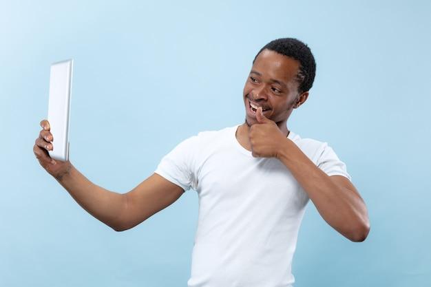 Do połowy długości bliska portret młodego mężczyzny afro-amerykańskiego w białej koszuli na niebieskim tle. ludzkie emocje, wyraz twarzy, reklama, sprzedaż, koncepcja. używanie tabletu do selfie, vloga, rozmowy.