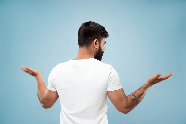 Do połowy długości bliska portret młodego mężczyzny hindusów w białej koszuli na niebieskim tle. ludzkie emocje, wyraz twarzy, koncepcja reklamy. negatywna przestrzeń. pokazywanie pustego paska, wskazywanie, wybieranie, zapraszanie.
