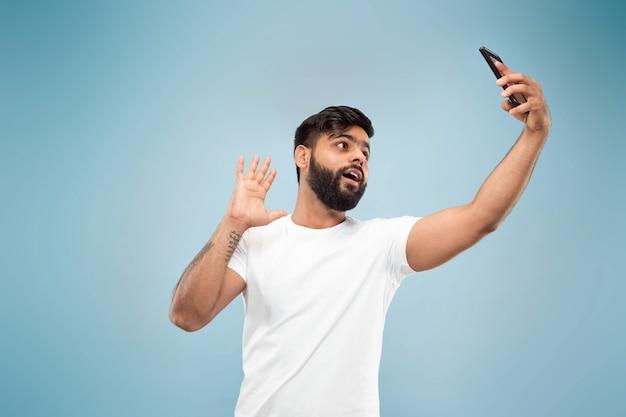 Do połowy długości bliska portret młodego mężczyzny w białej koszuli na niebieskiej ścianie