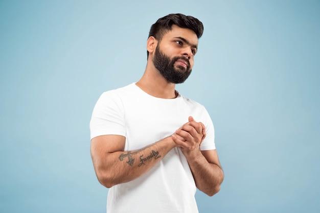 Do połowy długości bliska portret młodego mężczyzny w białej koszuli na niebiesko