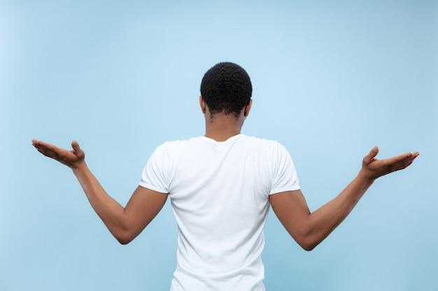Do połowy długości z bliska portret młodego afro-amerykańskiego modelu męskiego w białej koszuli na niebieskiej ścianie. ludzkie emocje, wyraz twarzy, koncepcja reklamy. wątpliwości, pytanie, niepewność.