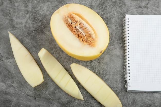 Do połowy pokrojony świeży słodki melon i pusty notatnik na marmurowej powierzchni.