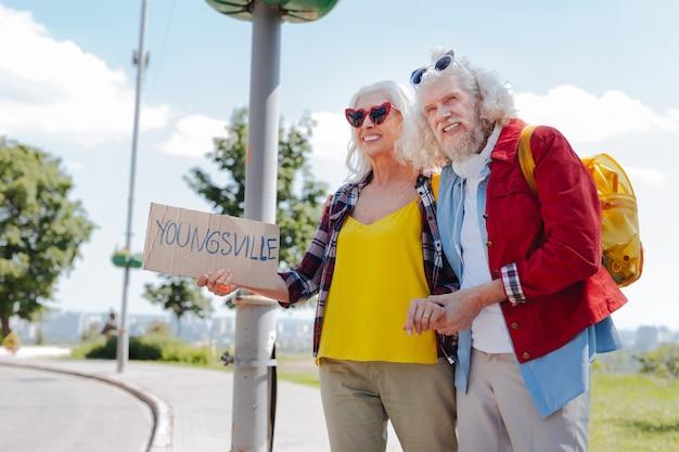 Do przygód. szczęśliwa para starszych stojących przy drodze podczas autostopu