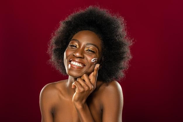 Do skóry. zachwycona afro amerykanka uśmiechnięta, nakładając krem na policzek