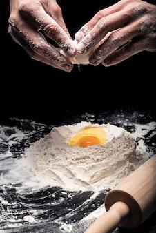 Do świeżej piekarni. zbliżenie młodych mans ręce przy użyciu jaj podczas robienia ciasta i pracy jako kucharz.