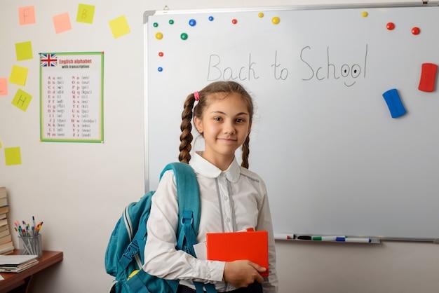 Do szkoły przyszła piękna uczennica z plecakiem i książką