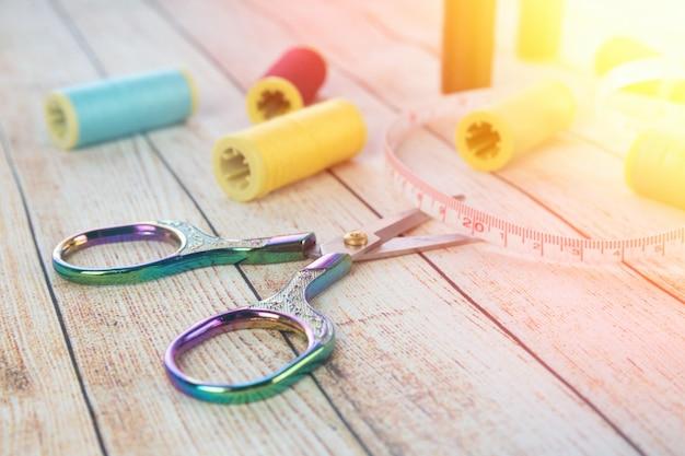 Do szycia tło. akcesoria do robótek ręcznych na drewnianym tle. szpulki nici, nożyczki, guziki, taśma miernicza, materiały krawieckie. zestaw do robótek ręcznych widok z góry