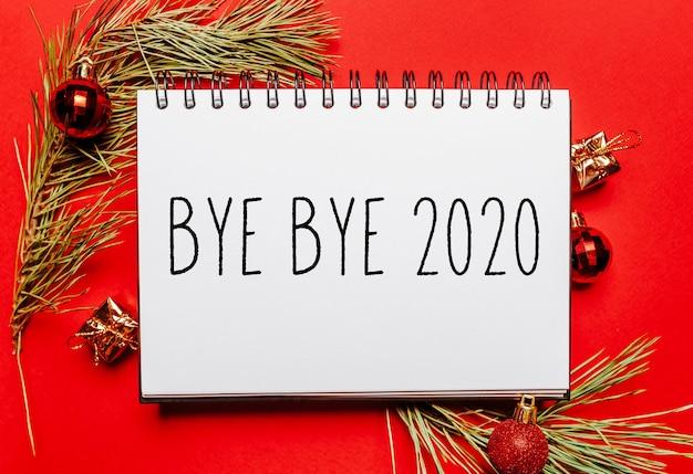 Do widzenia 2020 świąteczna kartka z gałązką jodły i zabawką na czerwono