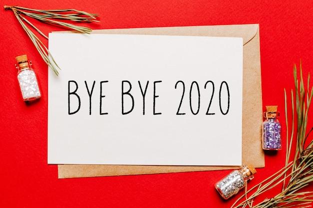 Do widzenia, 2020 świąteczna notatka z gałązką jodły na czerwonej koncepcji nowego roku