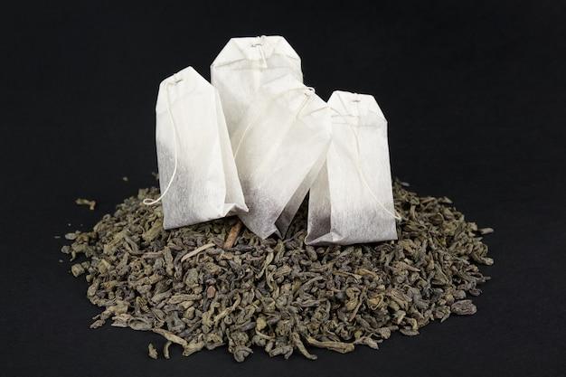 Do wyboru między zieloną herbatą liściastą a herbatą w kieszeniach. cztery paczki na stosie suchej dużej herbaty liściastej.