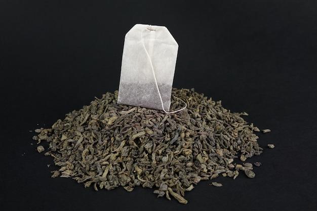 Do wyboru między zieloną herbatą liściastą a herbatą w kieszeniach. paczka na stercie suchej dużej herbaty liściastej.