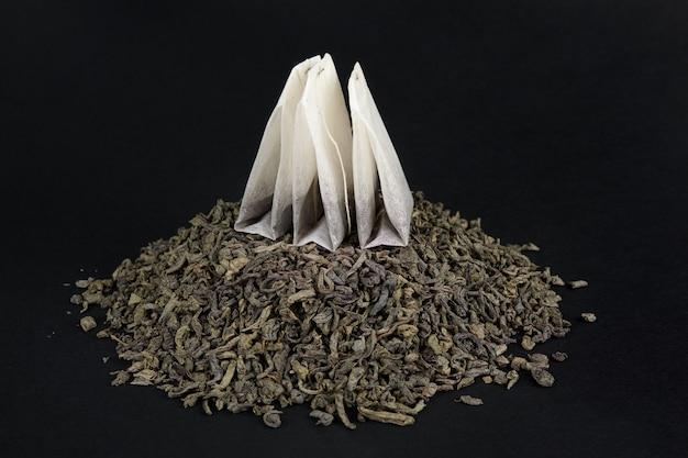 Do wyboru między zieloną herbatą liściastą a herbatą w kieszeniach. trzy opakowania na stosie suchej dużej herbaty liściastej.