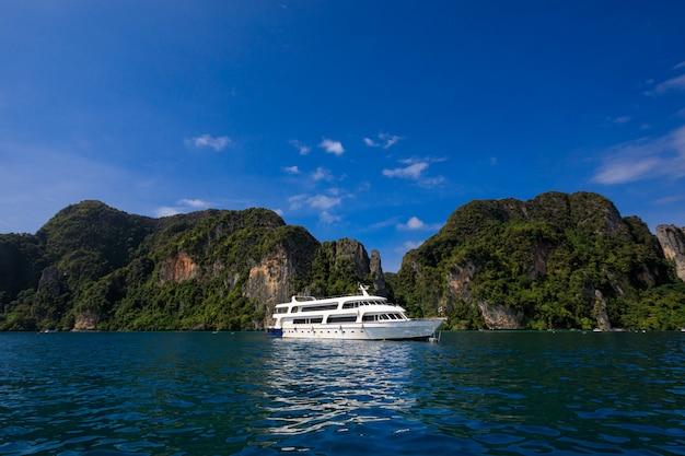 Do wynajęcia biała łódź na dennej wysokiej sezon podróży turysty i góry falezie z niebieskim niebem na phi phi wyspy kra bi tajlandia