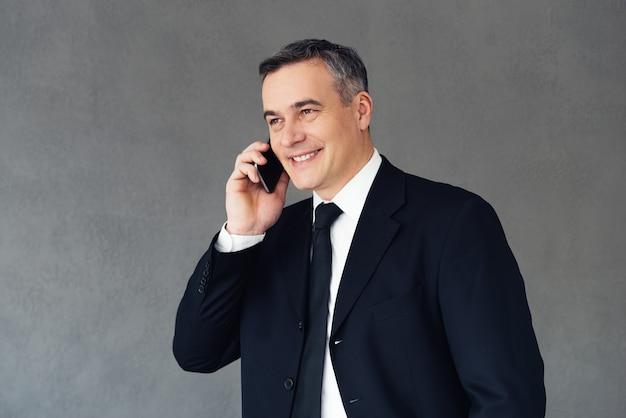 Do zobaczenia jutro! dojrzały biznesmen rozmawia przez telefon komórkowy z uśmiechem stojąc na szarym tle