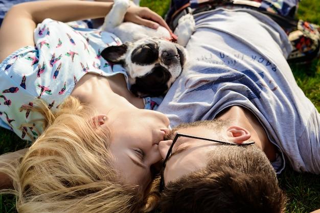Dobiera się całowanie, kłama z francuskim buldogiem na trawie w parku