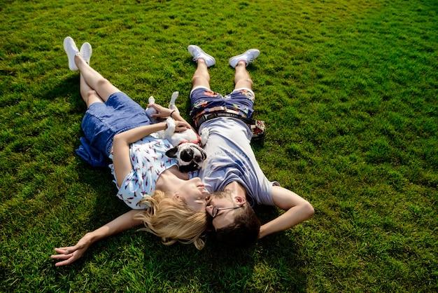 Dobiera się lying on the beach z francuskim buldogiem na trawie w parku