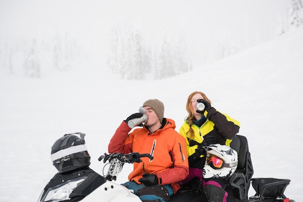 Dobiera się mieć kawę od termosu podczas gdy relaksujący w skuterze śnieżnym