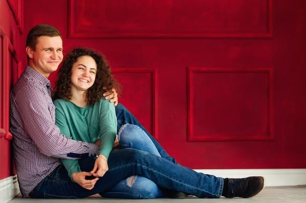 Dobiera się mieć zabawę podczas gdy siedzący na podłoga nad dekorującą czerwieni ścianą