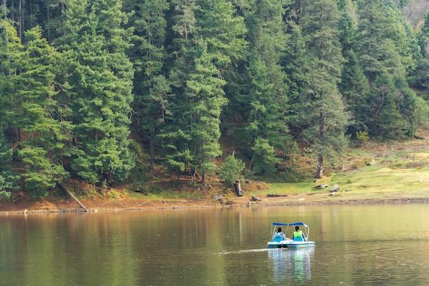 Dobiera się na małej łódce w jeziorze