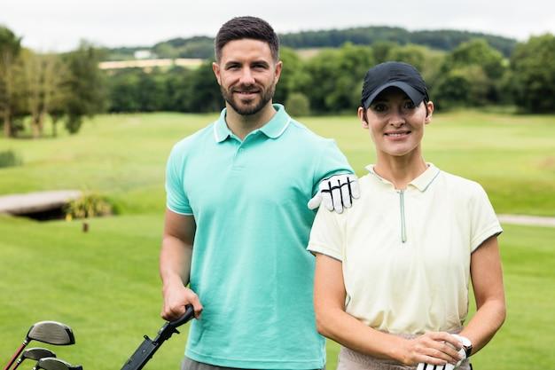 Dobiera się pozycję z kijem golfowym i torbą w polu golfowym