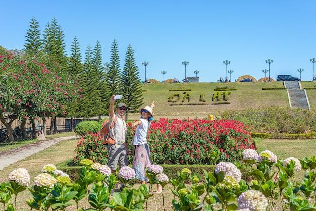 Dobiera się selfie na miasto parku wśród kwiatów przy da lat miasteczkiem, wietnam. mężczyzna z plecakiem i kobietą z wietnamskim kapeluszem ma zabawę