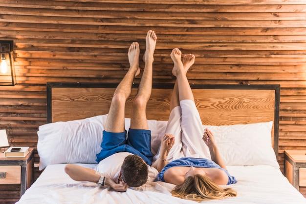 Dobiera się trzymać each inny ręki lying on the beach na łóżku
