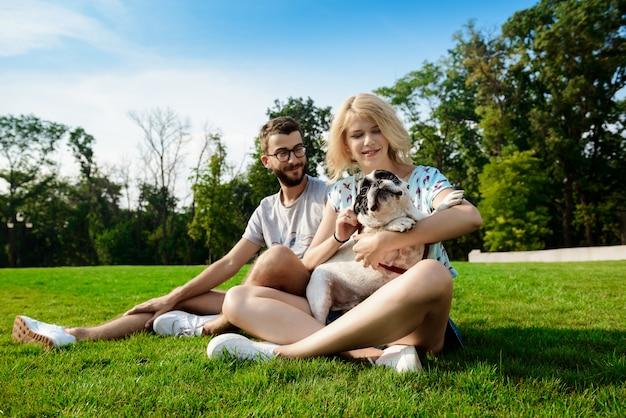 Dobiera się uśmiecha się, siedzący na trawie z francuskim buldogiem w parku