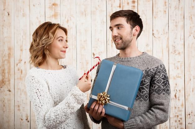 Dobiera się uśmiechniętych mień bożych narodzeń cukierek i prezent nad drewnianą ścianą