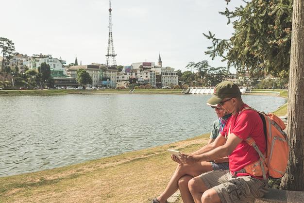 Dobiera się używać pastylka mądrze telefon w zielonym miasto parka jeziorze przy da lat miasteczkiem, wietnam. mężczyzna z plecakiem i kobieta z wietnamskim kapeluszem