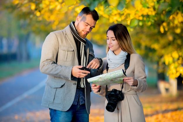 Dobiera się z mapą i kamerą w miasto jesieni alei.