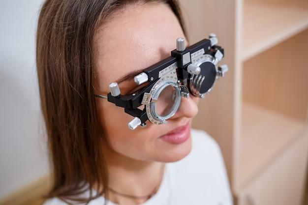 Dobór okularów na wzrok dla kobiety. prawidłowy dobór punktów. salon optyczny. optyk. próbne soczewki.