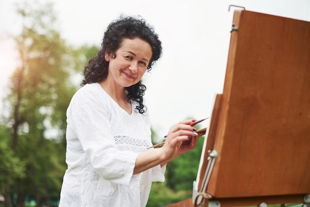 Dobra atmosfera. portret dojrzały malarz z czarnymi kręconymi włosami w parku na świeżym powietrzu
