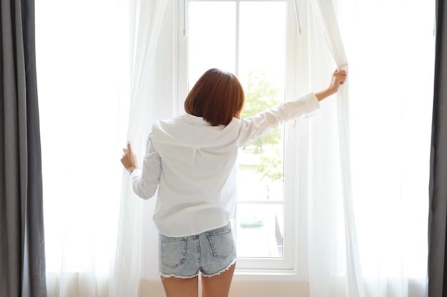 Dobra forma i zdrowa, młoda kobieta azjatycka budzi się rano o wschodzie słońca.